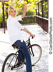 middle aged woman on a bike waving - cheerful middle aged...