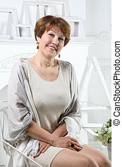 Middle aged woman on a chair in the living room