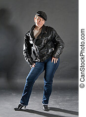 Middle aged woman posing as rock star with guitar in studio