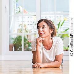 Middle aged woman serious face thinking about question, very confused idea