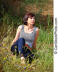 Middle aged woman sitting in long dry summer grass.