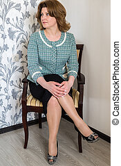 middle-aged woman sitting on chair in living room