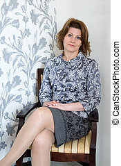 middle-aged woman sitting on chair in the living room
