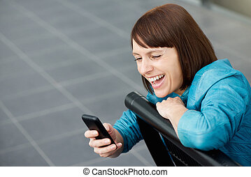 Middle aged woman smiling at mobile phone