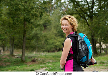 Middle aged woman smiling with bicycle