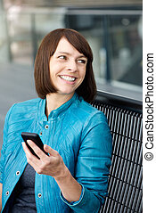 Middle aged woman smiling with cell phone