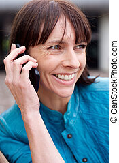 Middle aged woman smiling with mobile phone