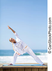 middle aged woman stretching on beach - fitness middle aged...