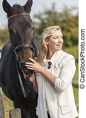 Middle Aged Woman Stroking Her Horse