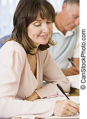 Middle aged woman studying with other adult students