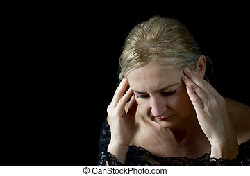 Middle aged woman supporting her head by hands