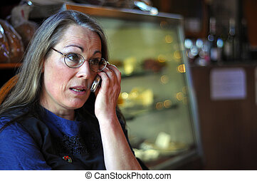 Middle aged woman talking on cell phone inside a shop