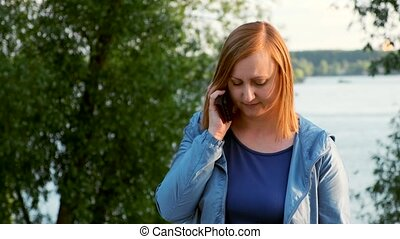 Middle-aged woman talking on the phone. Background of the river bank and trees