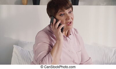 Middle aged woman using cellular at home - Attractive,...