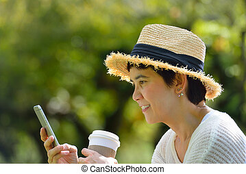 Middle aged woman with a mobile phone in the park