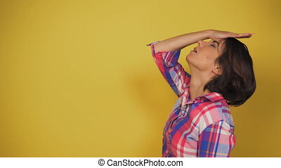 Middle aged woman with brown hair is upset about something. Girl stand on the yellow background. High quality 4k footage