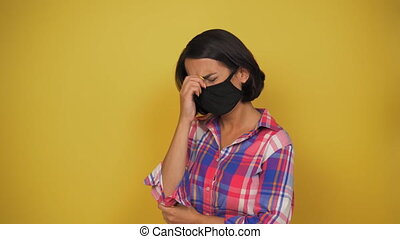 Middle aged woman with brown hair wear black pollution mask...