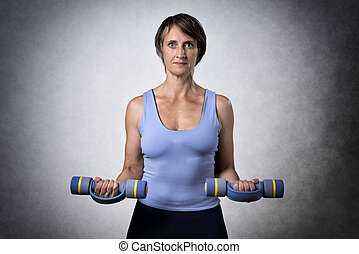 Middle aged woman with dumbbells