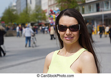 middle aged woman with sunglasses in pedestrian street