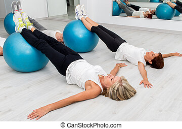 Middle aged women doing leg exercises with fitness balls.