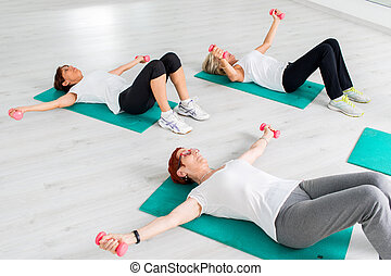 Middle aged women doing workout with weights.