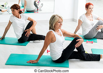 Middle aged women warming up in gym.