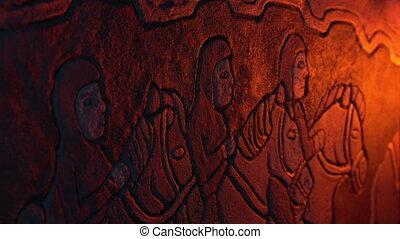 Firelight illuminates an old wall mural of men on horseback