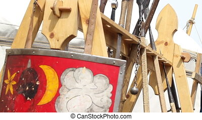 Different medieval weapons arranged in a wooden rack.