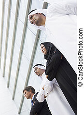 Middle Eastern and Caucasian business workers standing outside a