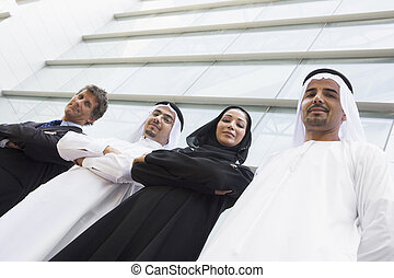 Middle Eastern and Caucasian business workers standing...