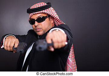 middle eastern bodyguard posing with guns on black...