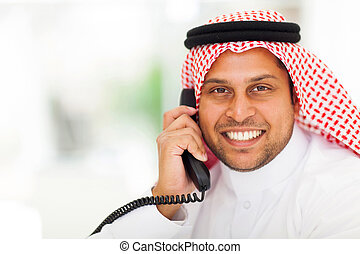 middle eastern business man answering telephone - smiling...