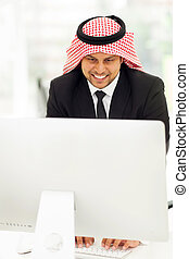 middle eastern businessman working on the computer - happy...
