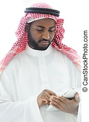 Middle eastern man with gulf clothes using tablet at office