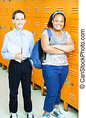 Middle school boy and girl in the hallway by their lockers.