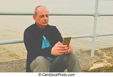 Midle aged man sitting on the shore of the lake. Solitude mature man using mobile phone on the bank. Concept of activ man