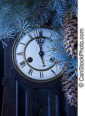 midnight antique clock and a Christmas tree with pine cones
