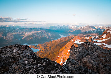 Scenic aerial view from top of mountain on valleys and mountains covered in midnight sun near Narvik in Norway.