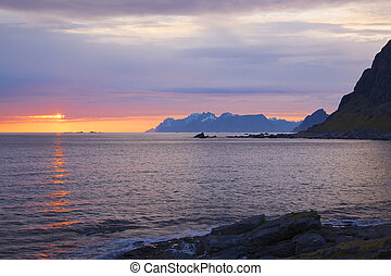 Scenic midnight sun over the ocean on Lofoten islands in Norway during polar day