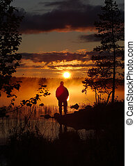 Man watching midnight sun in Finland by the lake Inari