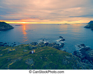 Scenic view of midnight sun on rocky coast of Vesteralen inslands in Norway