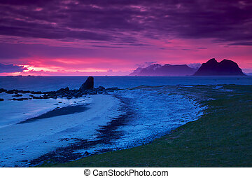 Picturesque panorama of white sand beach lit by midnight sun on Lofoten islands in Norway
