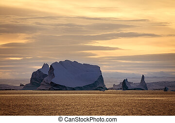 Icebergs and midnight sun in Scoresbysund in eastern Greenland