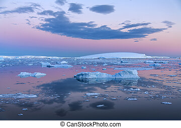 The Midnight sun over the icebergs in the Weddell Sea near the Antarctic Peninsula in Antarctica.
