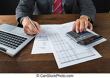 midsection, de, homem negócios, verificar, contas, escrivaninha
