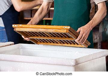 midsection, de, trabalhador, imergindo, molde, em, pulpy, água