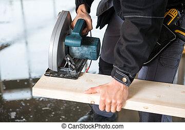 midsection, di, carpentiere, usando, sega elettrica, tagliare, legno