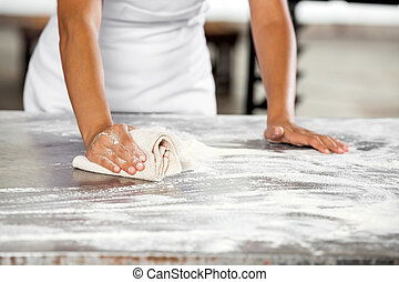 Midsection Of Baker Cleaning Flour From Table