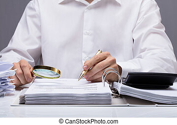 Businessman Examining Invoice With Magnifying Glass