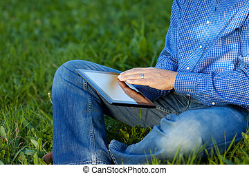 Midsection Of Businessman Using Digital Tablet On Grass